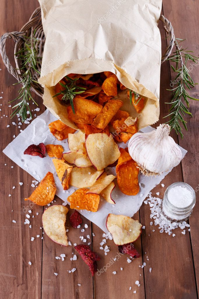 Healthy vegetable chips on paper with sea salt, rosemary and garlic
