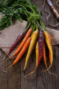Colored carrots over rustic wooden background