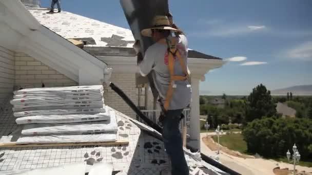 člověk nese dodávky střešní krytiny na střeše