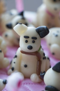 Dalmatian puppy made of marzipan with sausages in a teeth