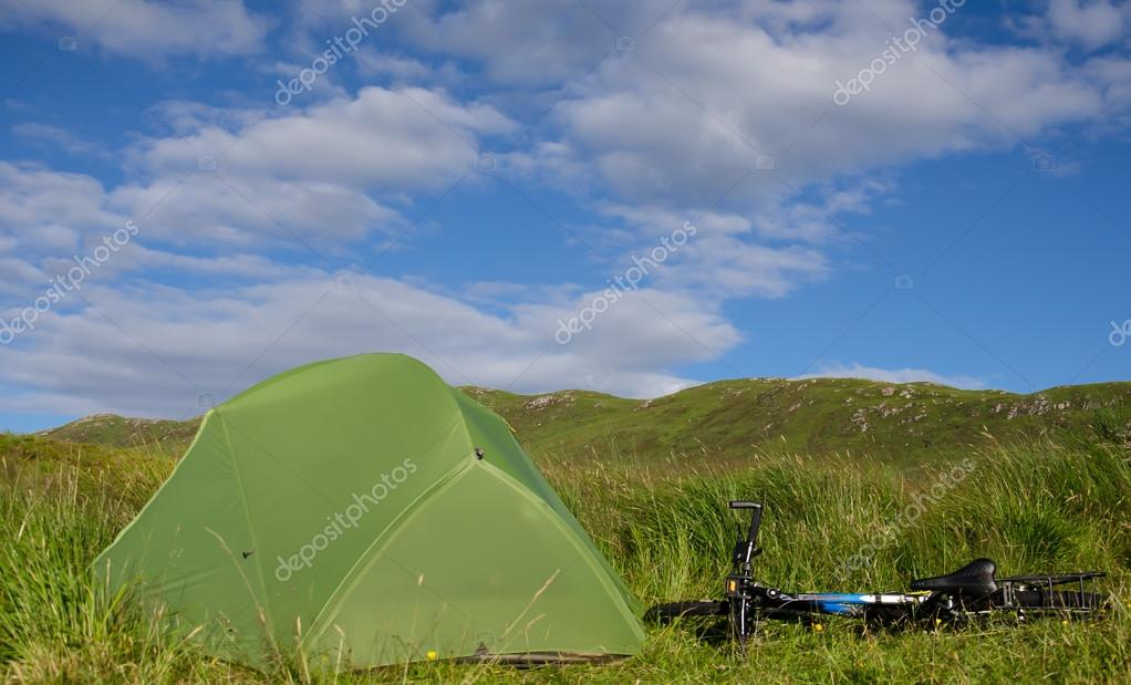pitched tent on meadow near mountain bike