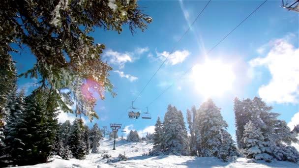 sonniger Tag im verschneiten Berg und Skilift fährt mit Skifahrern auf.