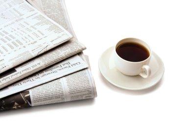Coffee cup near  newspaper