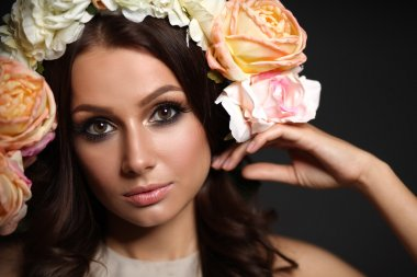 Portrait of a beautiful woman with flowers in her hair. Fashion photo