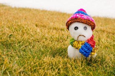 Unhappy snowman melting on green grass