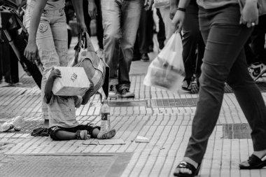 Poor little boy sitting on the street