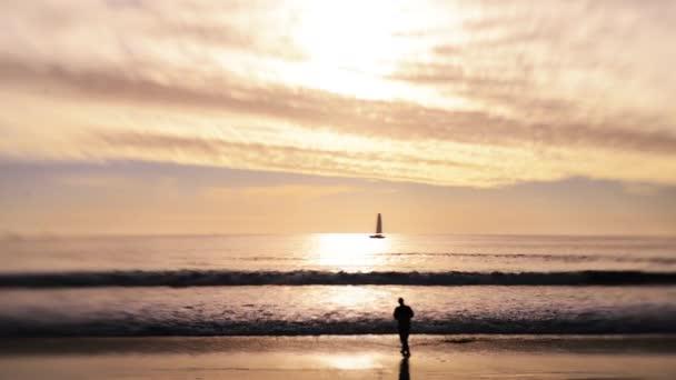Halász a partján a naplemente a strandon elhaladó vitorlás