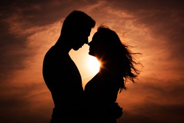 Couple in love silhouette during sunset - touching noses