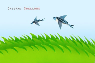 Green field with origami swallows