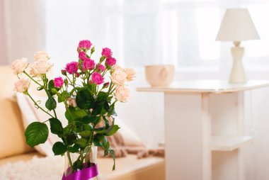Bouquet of flowers in a room in the interior. Red and white rose in a vase on a table in a bright room.