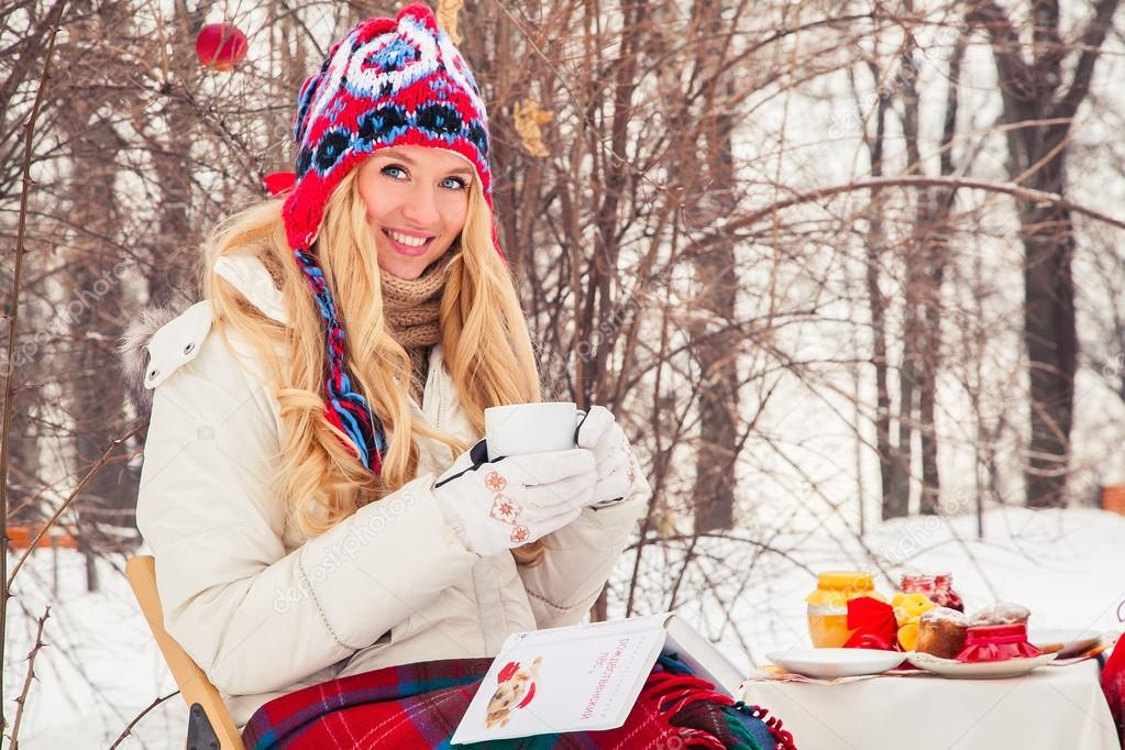 Portrait of a beautiful woman is drinking tea or coffee in the fresh air in the winter.