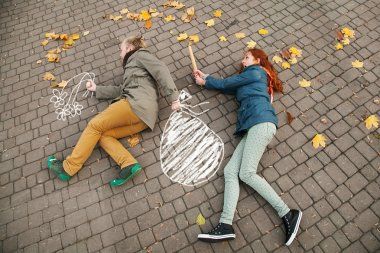 Love story. Autumn Park. Man and woman in a city park tells the story of his love. Painted on earth concept litters loving couple. Man escapes with a painted bag from his woman.