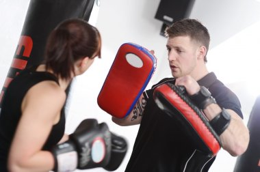 Woman punching pads with trainer