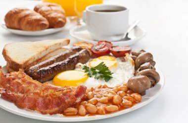 Traditional english breakfast - plate with fried eggs, sausages, beans, mushrooms and bacon, cup of fresh coffee, croissants and orange juice on white background stock vector