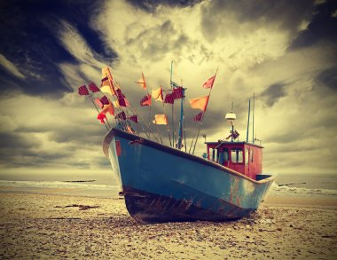 Small fishing boat on shore of the Baltic Sea, vintage retro ins