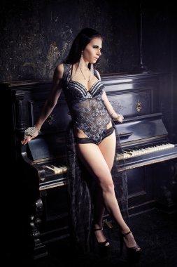 beautiful woman sitting on a black studio piano