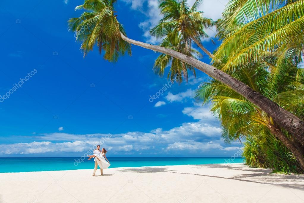 Young loving couple on tropical beach with palm trees, wedding o