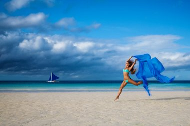 Beautiful young woman jumping on the beach with a blue tissue