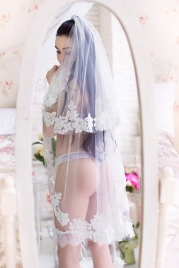 Beautiful young bride in the veil, and with garter stands in fro