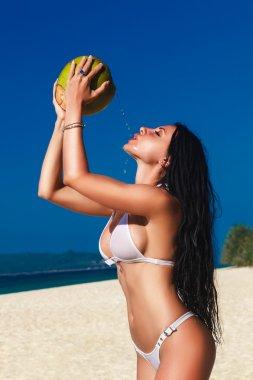Young beautiful woman with long black hair in white bikini, drin