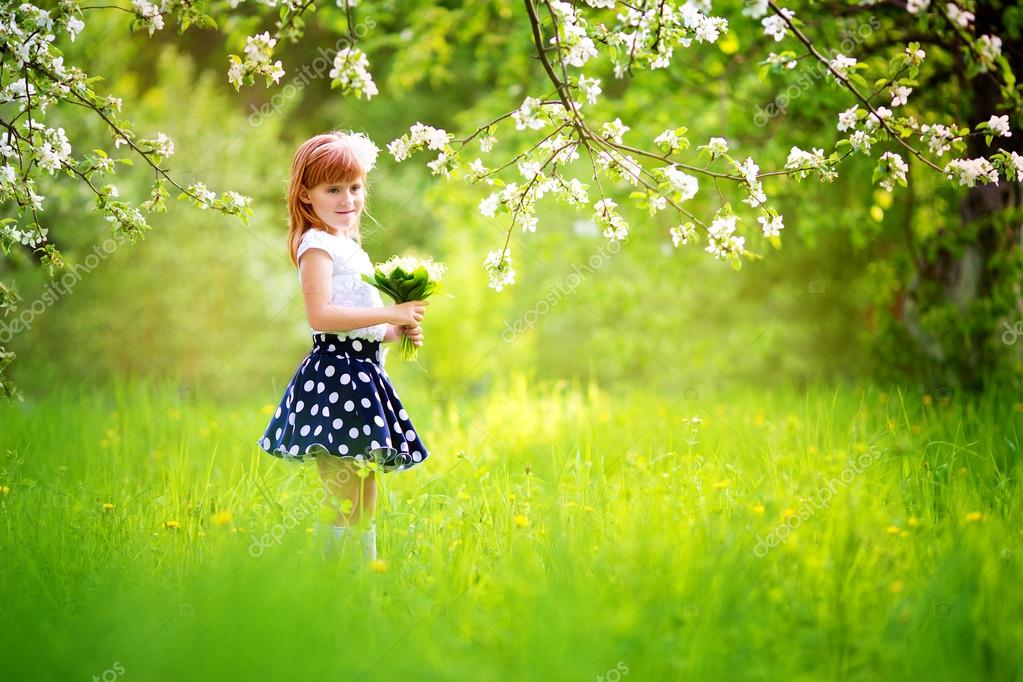 Happy little girl with a bouquet of lilies of the valley having