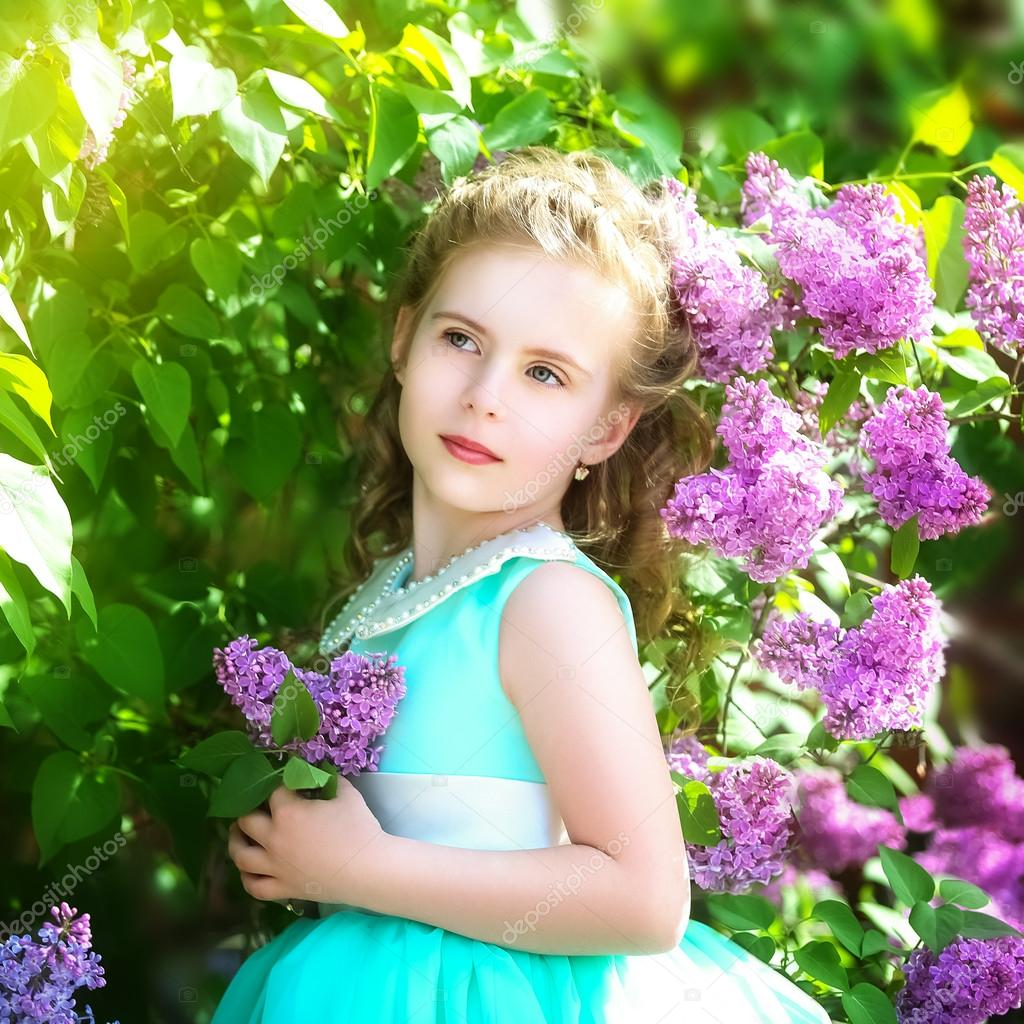 Beautiful little girl in a blue dress with a large white bow in