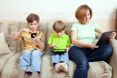 Two brothers and mother sit on divan
