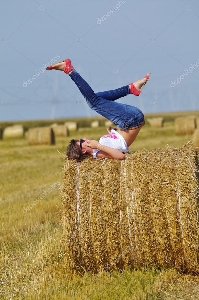 Young woman relaxing on hay bale