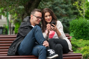 Two friends sharing a smartphone on a park bench