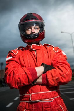 Racer wearing red racing protective suit and helmet