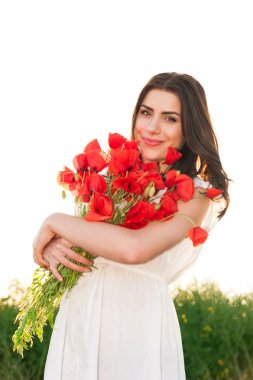 Beautiful woman over Sky and Sunset in the field holding a poppies bouquet, smiling
