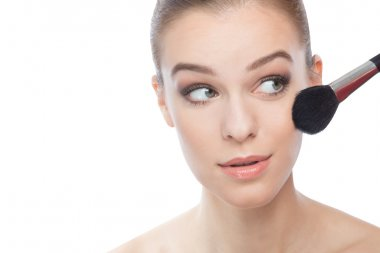 Woman with make-up brush, looking on her left with copyspace on