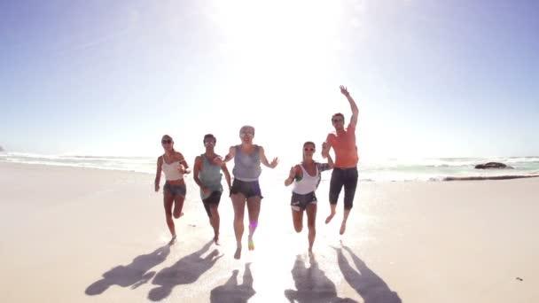 přátel běhu a skákání do kamery na pláži