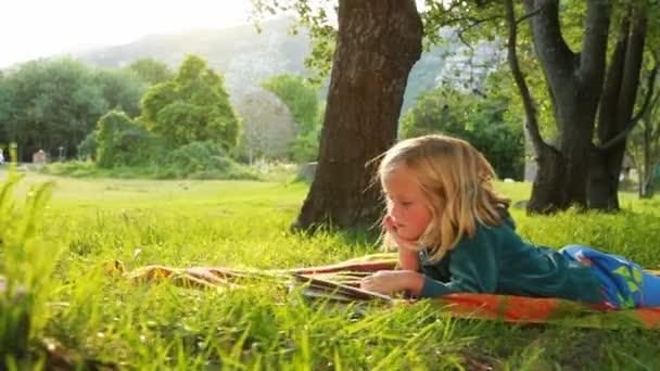 holčička čte knihu v parku