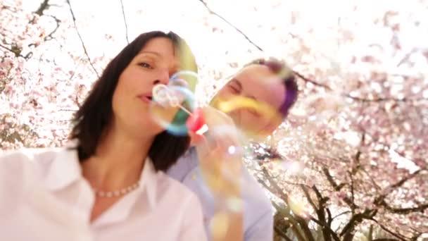 atraktivní starší žena fouká mýdlové bubliny