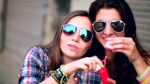 Girls with sunglasses having fun making bubbles