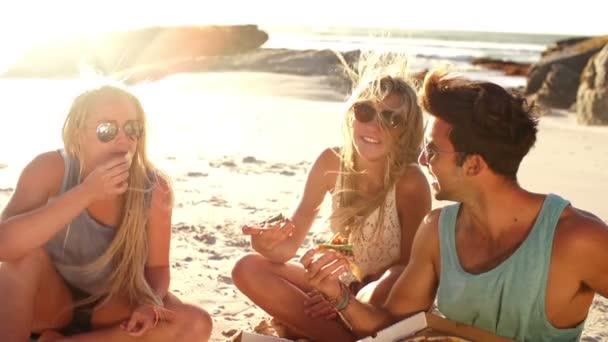 přátel, jíst pizzu na pláži