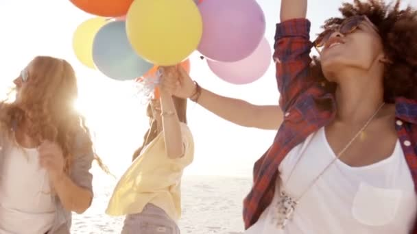 Friends playing with balloons on beach