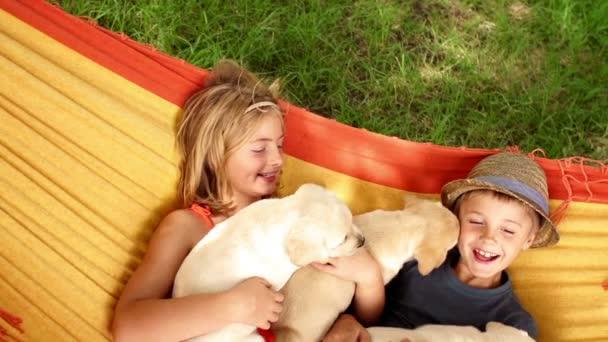 děti s štěňata leží v houpací síti