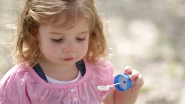 Little girl having fun blowing soap bubble