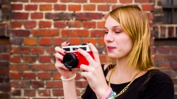 Teenage woman having fun taking pictures with old camera
