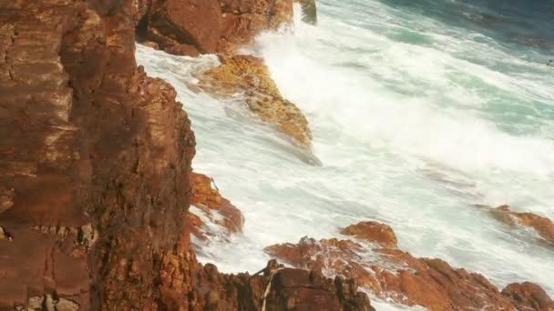 hullámok, aprítás és a borulás sziklák a tengerparton