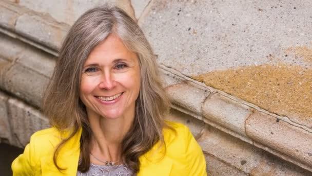 zralá žena v jejím 50s se usmívá na kameru
