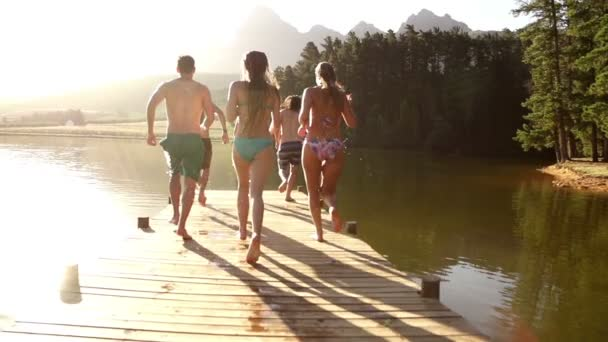 Friends running and jumping into lake