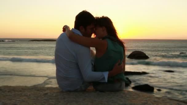 pár v lásce se sedí na skále u moře