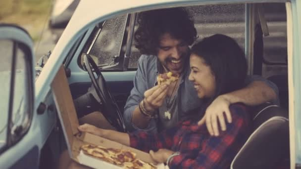 Couple eating pizza in retro car