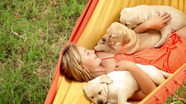 Happy girl holding labrador puppies while swinging in hammock