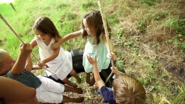Group of kids swinging on tire