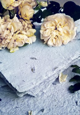 White roses, petals and handmade paper