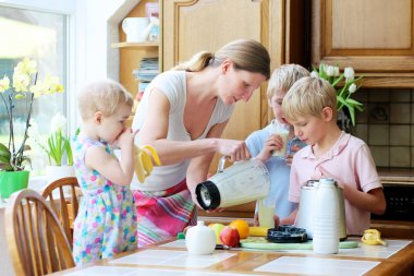 Mother with three kids preparing drink with milk and fruits